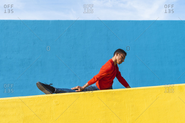 Young dancer stretching on yellow wall
