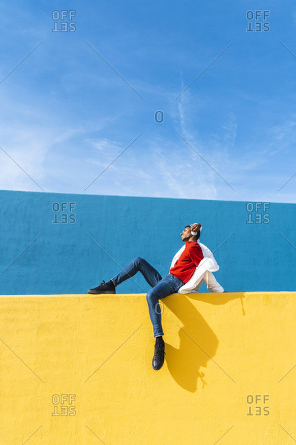 Young dancer sitting on yellow wall- listening music