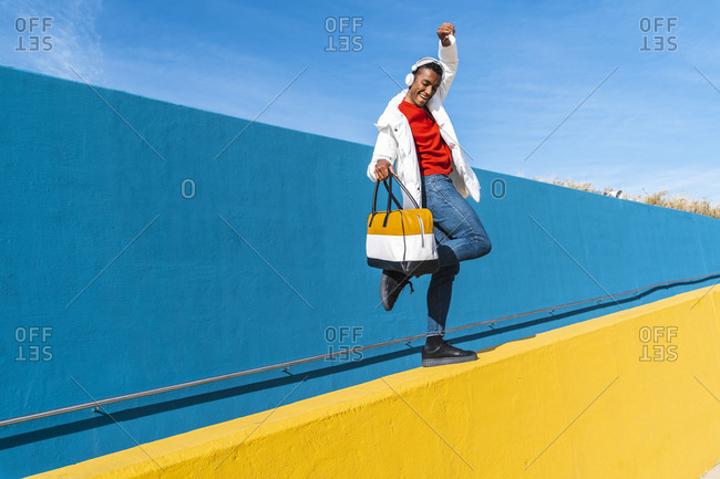 Young man with bag- dancing carefree on a yellow wall
