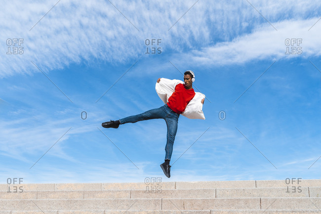 Young man moving and dancing on stairs outdoors
