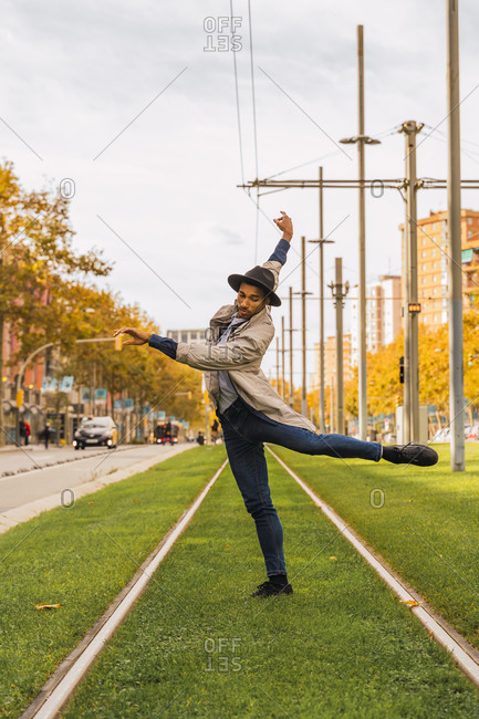 Young man moving and dancing on tram rails