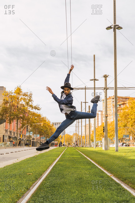 Young man jumping and dancing on tram rails