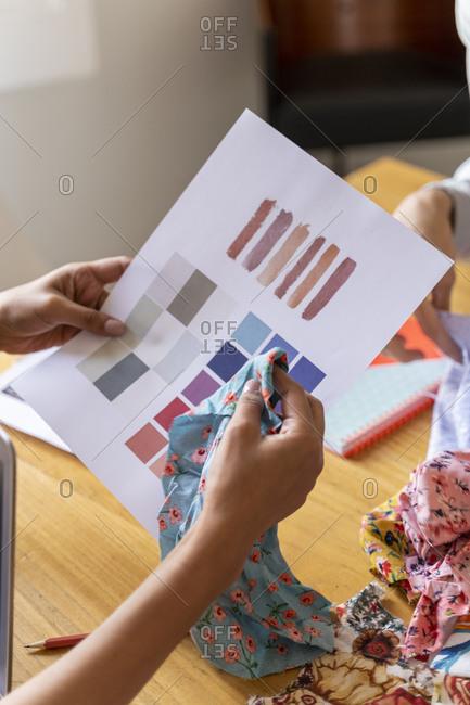 Fashion designer holding color sample in office