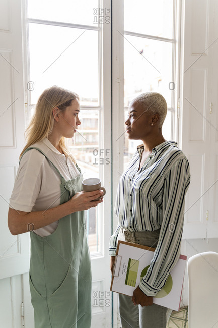 Two women with documents and cup of coffee standing at the window