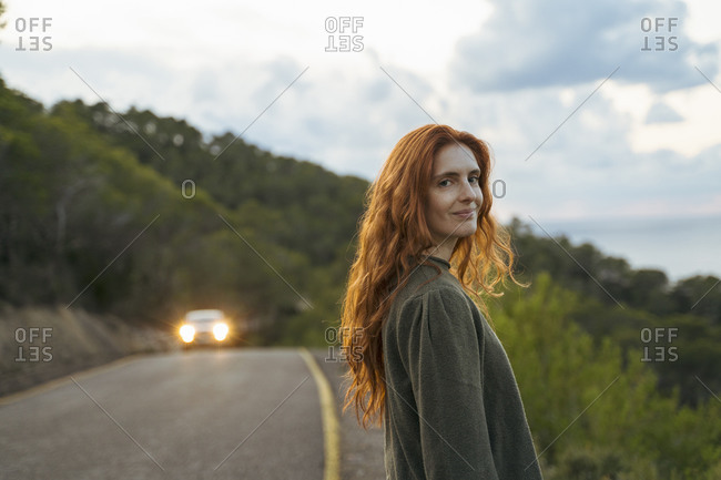 Portrait of redheaded young woman at a country road at dusk- Ibiza- Spain