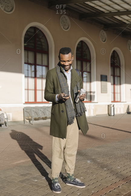 Stylish man with reusable cup using smartphone while waiting for the train