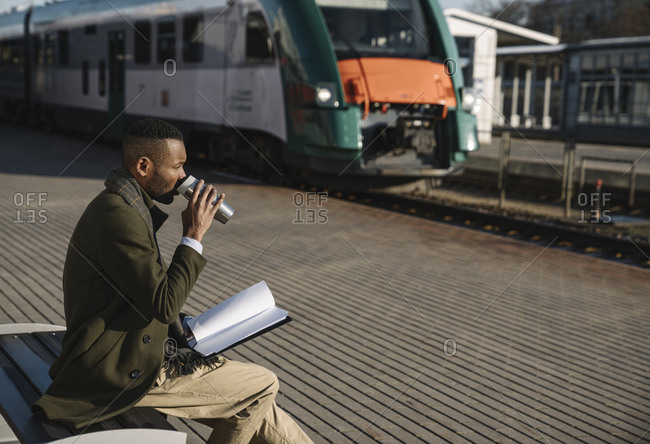 Stylish businessman drinking hot drink from reusable cup while waiting for the train