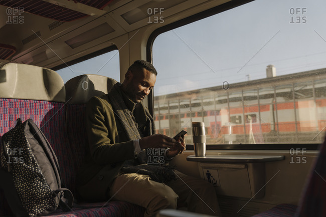 Stylish man using smartphone inside a train