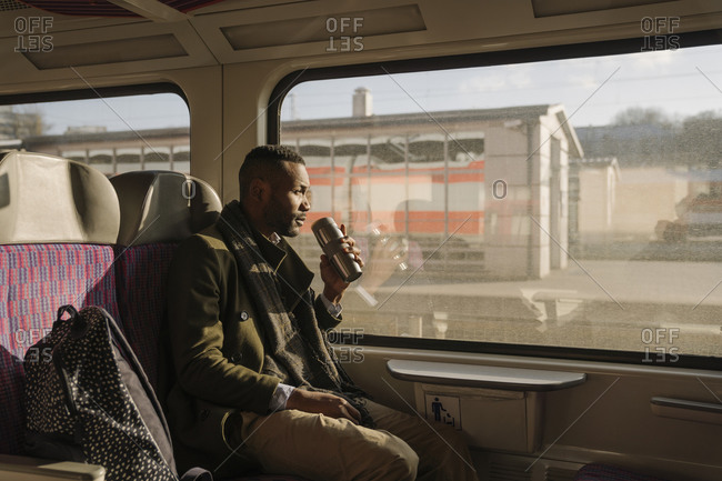 Stylish man drinking hot drink from reusable cup while traveling by train