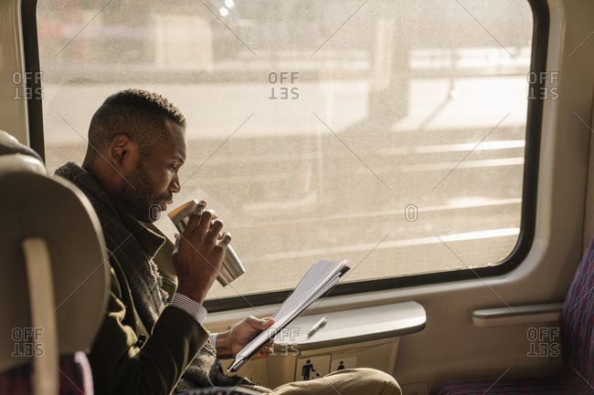 Stylish businessman with reusable cup and documents in a train