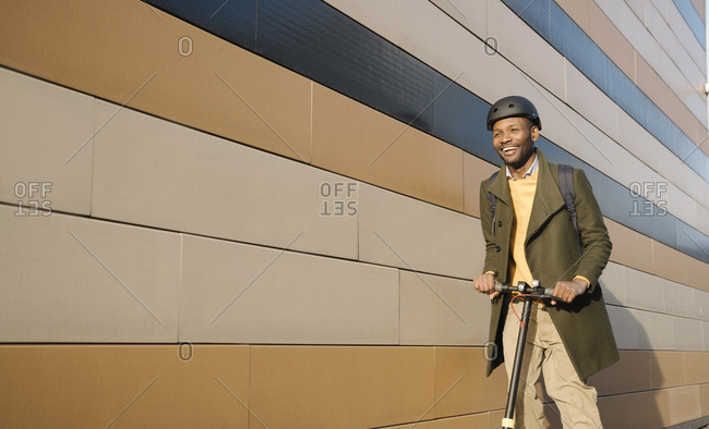 Happy man with helmet and scooter passing a building