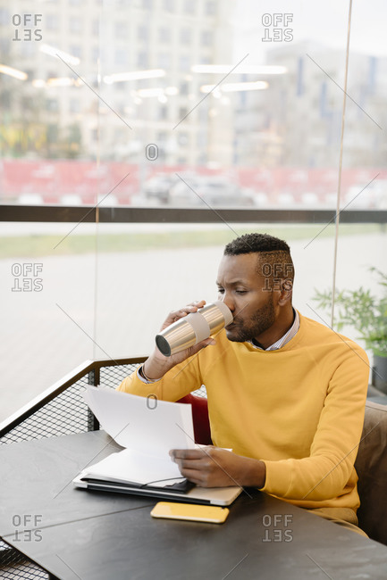 Man drinking hot drink from reusable cup while reading documents in a cafe
