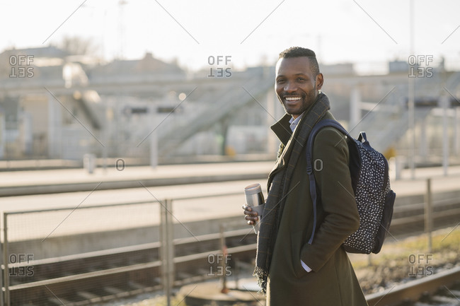 Portrait of smiling man with reusable cup waiting for the train