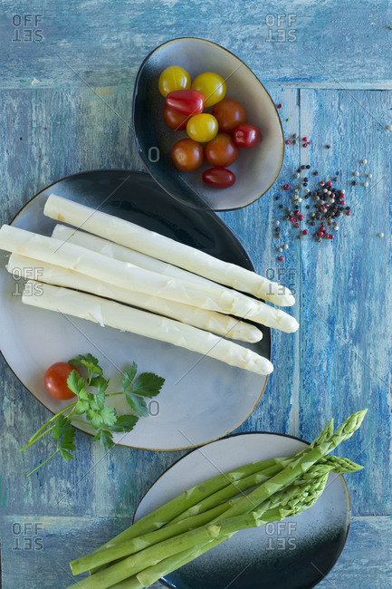 White and green asparagus on rustic wooden background- yellow tomatoes- red tomatoes- colored pepper- parsley