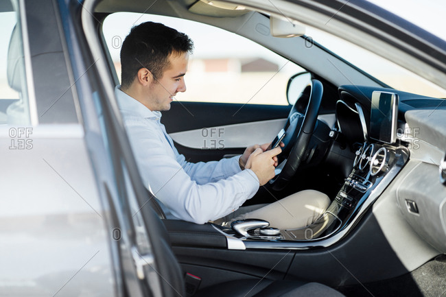 Smiling young businessman using smartphone in car