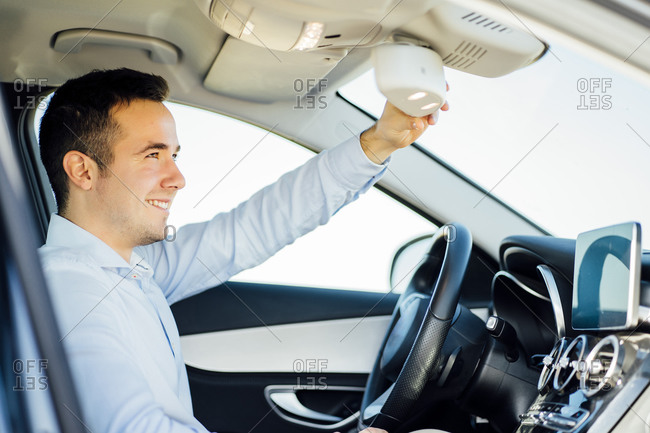 Smiling young businessman adjusting rear-view mirror in car