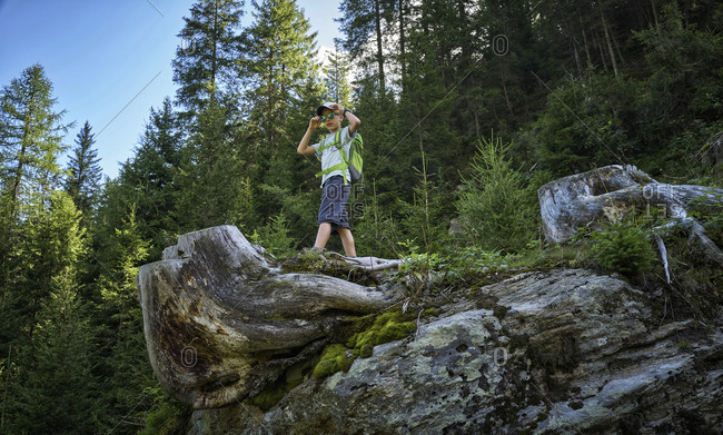 Boy standing on tree log during a hiking trip in alpine scenery- Passeier Valley- South Tyrol- Italy