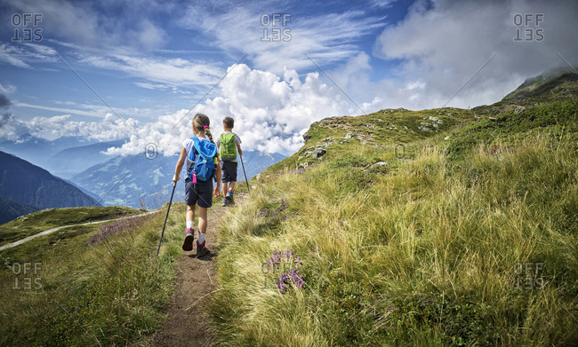 Boy and girl hiking in alpine scenery- Passeier Valley- South Tyrol- Italy