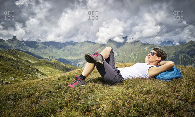 Woman having a break from hiking lying on alpine meadow- Passeier Valley- South Tyrol- Italy