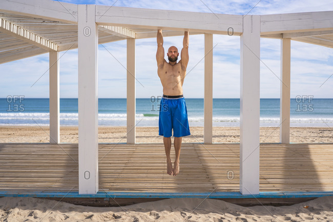 Sportsman training at the beach- chin-up