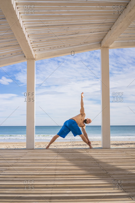Sportsman training at the beach- triangle pose