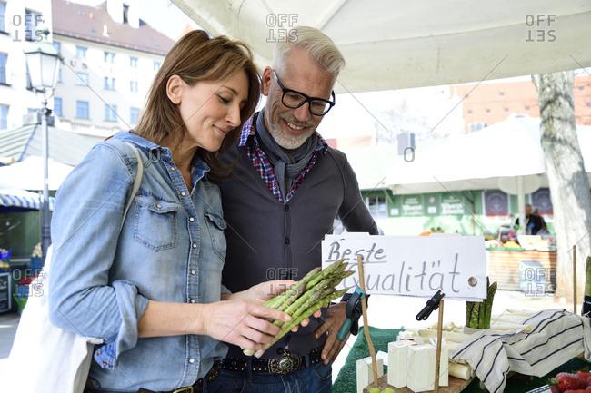 Mature couple choosing asparagus at a market stall