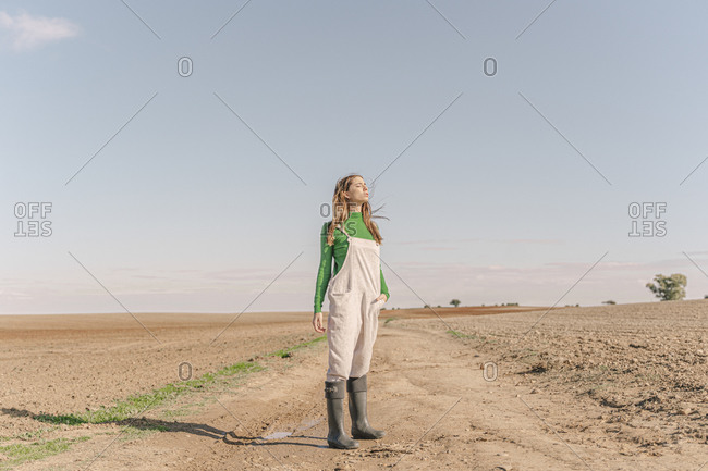 Young woman standing on dry field- with eyes closed
