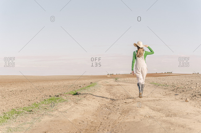 Young woman walking on dry field- rear view