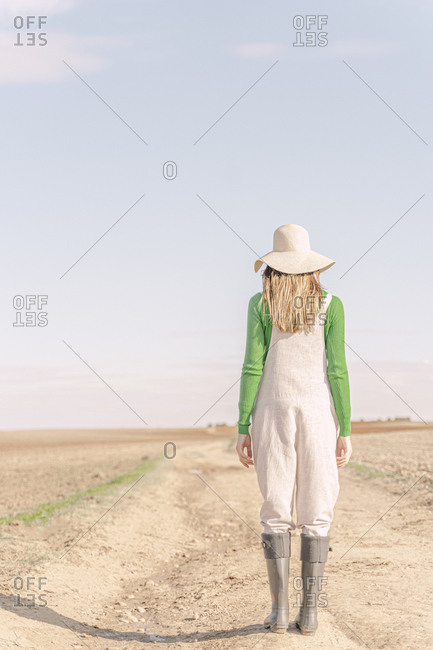 Young woman looking at dry field dry field- rear view