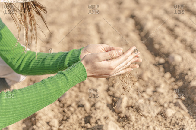 Soil trickling through hands of a woman