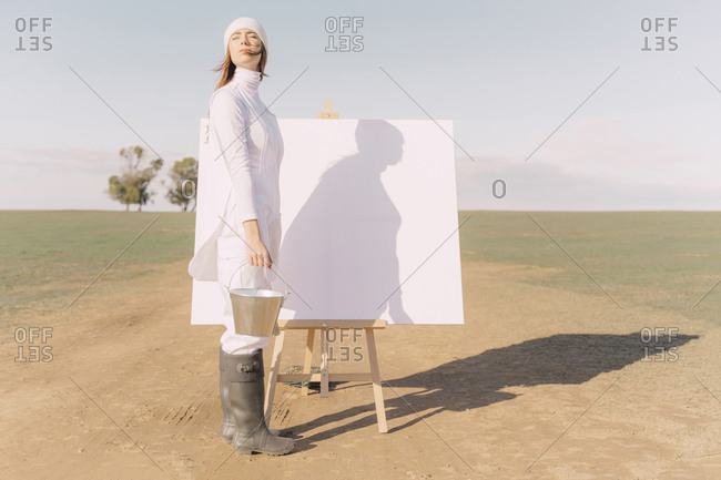 Young woman on dry field- starting to paint on white canvas