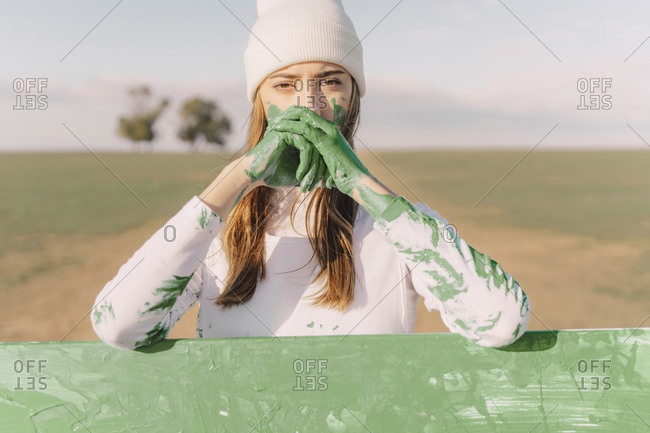 Young woman with green hands- leaning on painting