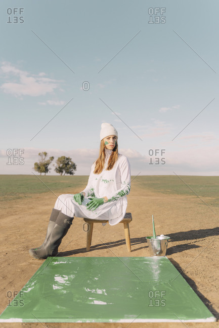 Young woman sitting on stool with green painting on dry field