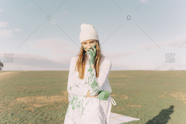 Young woman putting green painted hand on her face