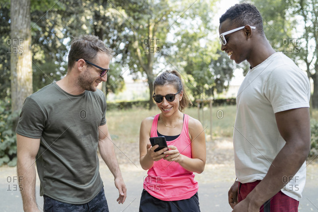 Friends having a break from exercising looking at smartphone