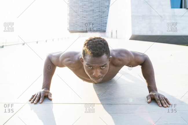 Barechested man doing push-ups at sunset