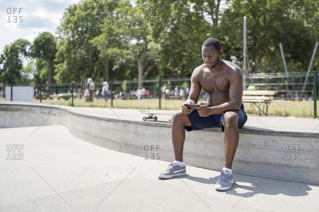 Man with skateboard using smartphone