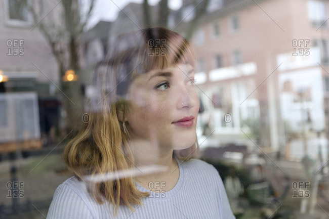 Portrait of young woman with nose piercing looking out of window