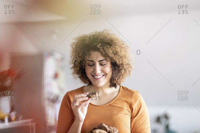 Smiling mid adult woman eating a cookie