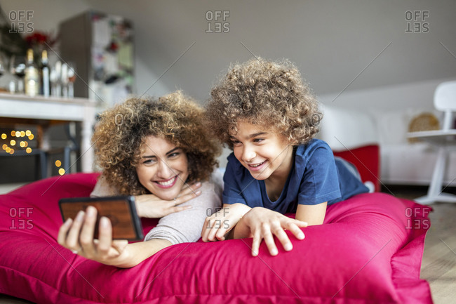 Mother and son watching a video on smartphone- lying on big pillow
