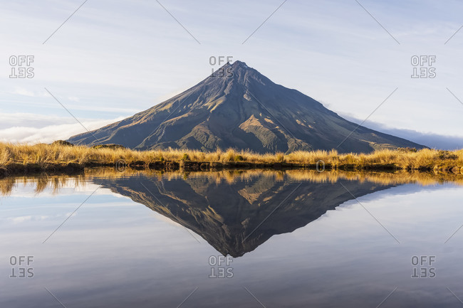 New Zealand- Mount Taranaki volcano reflecting in shiny lake at dawn