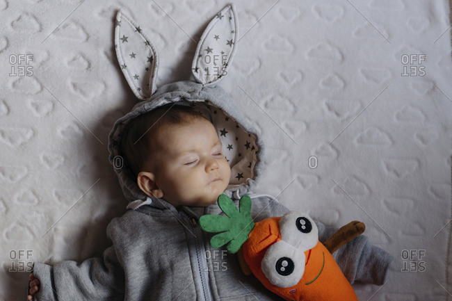 Portrait of sleeping baby girl in a rabbit hoodie lying on white blanket