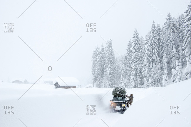 Austria- Salzburger Land- Lammertal- Man attaching Christmas tree to car roof on snowy road