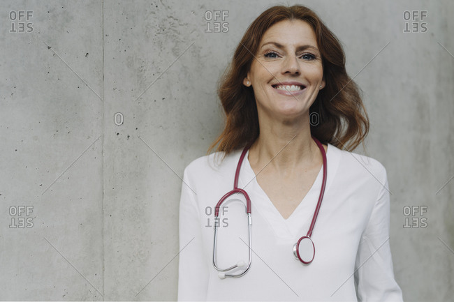 Portrait of a smiling female doctor at a concrete wall