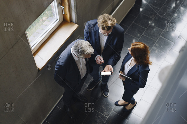 Business people with smartphone talking in modern office building