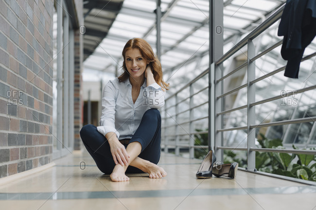Portrait of smiling businesswoman sitting on the floor in a modern office