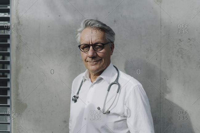 Portrait of a confident senior doctor at a concrete wall