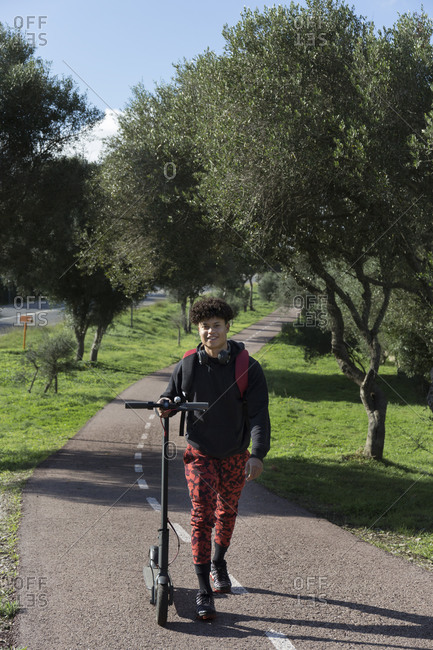 Portrait of smiling young man with e-scooter on bicycle lane