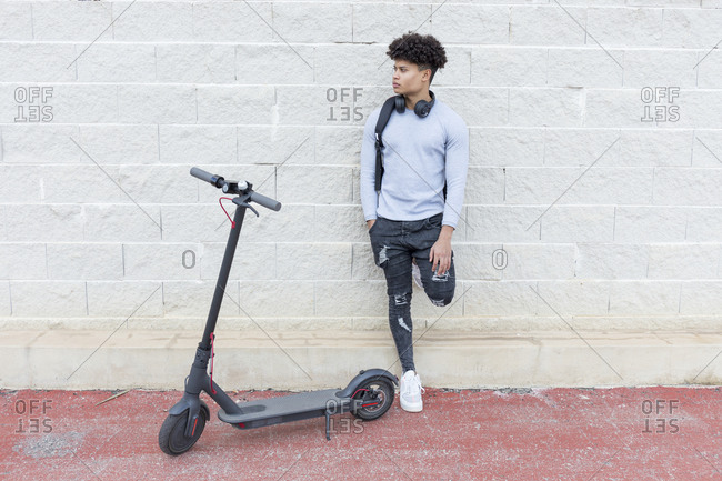 Young man with e-scooter outdoors