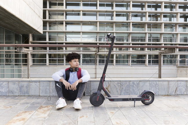 Young man with e-scooter sitting down in the city